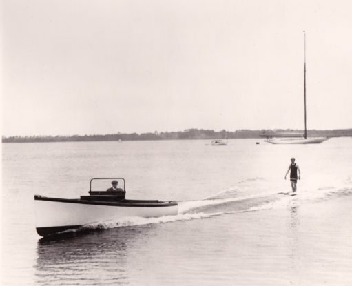 Image of man in an old fashioned swimsuit aquaplaning behind a small powerboat