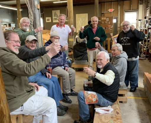 A group of smiling volunteers share a celebratory drink