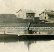 LIGHTNING (HMCo. #20), the United States Navy's first torpedo boat in Newport waters, 1876. Sepia tone photograph. Workshop buildings in the background. Torpedo boat in the foreground. Portside View of boat.
